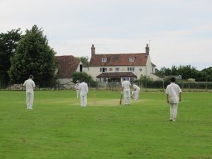 cricketers in front of a village pub